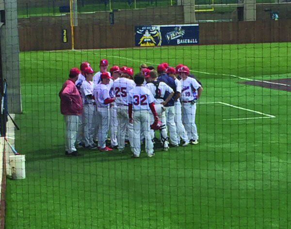 The LHS baseball team comes together in a huddle during their region game against Harrisburg.