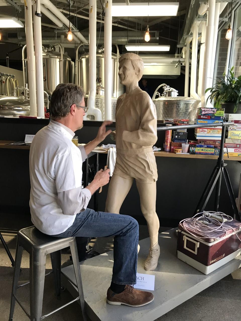 Sculptor Darwin Wolf works on a clay model of Rich Greeno.