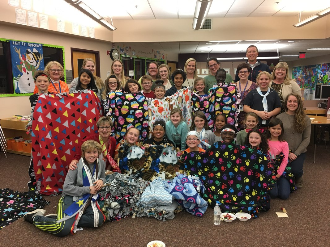 Students receiving blankets from Project Warm Up. Students from LHS spend time creating the blanket to give to people in need.