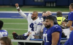 Dallas Cowboys quarterback Dak Prescott (4) lifts his fist to cheers from fans as he is carted off the field after season ending ankle injury.