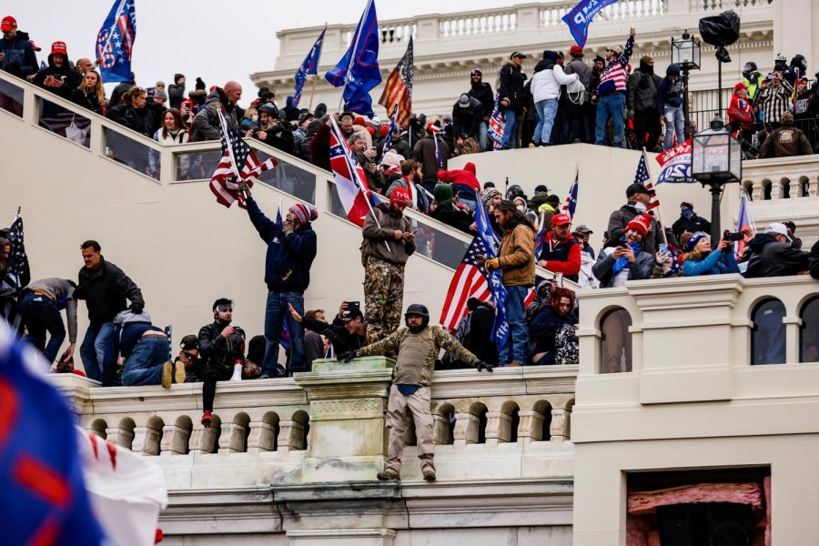 Rioters seen climbing the capitol  building and waving disruptive flags with no law enforcement in sight.