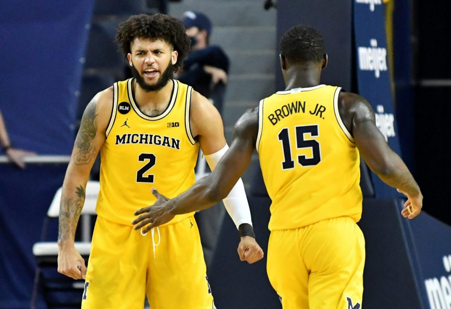 Michigan Seniors Isaiah Livers and Chaundee Brown Jr. celebrate a basket.