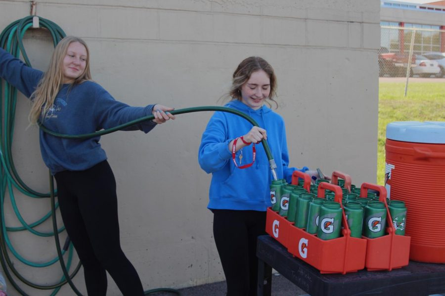 LHS football managers Allison Kolling and Madyson Lawson fill water bottles at practice.