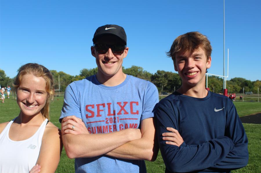 Senior captains of the LHS cross country team Hannah Dumansky and Kadin Groen smiling with their Coach, Luke Jelen.