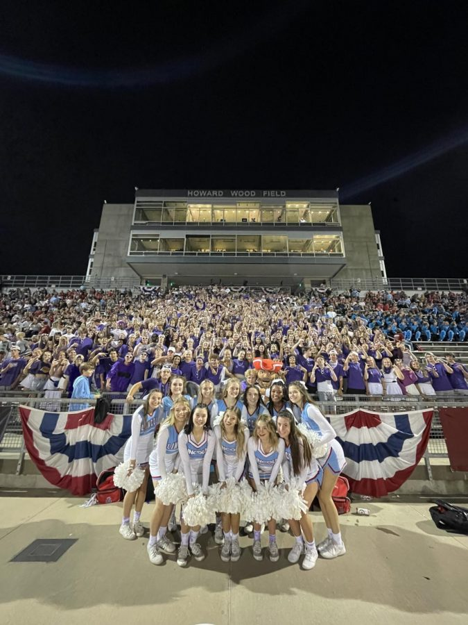 The LHS sideline cheer team poses in front of the sea of purple at the 2021 Presidents Bowl.